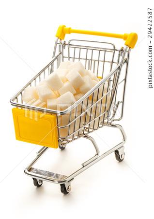 图库照片: supermarket pushcart with pile of white sugar