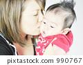 一個剛出生的嬰兒和一個年輕的母親親吻嬰兒的臉頰 990767