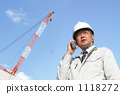 Middle businessman who makes radio communication at a construction site with a crane 1118272