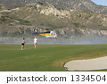 A helicopter descending into the water supply to the pond of the golf course for fire fighting activity 1334504