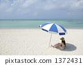 休息在沙滩伞下的泳装妇女 1372431