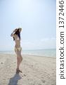 站立在一个白色沙滩的泳装妇女注视着天空 1372446