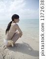 泳装妇女坐一个白色沙子海滩 1372638