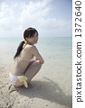 泳装妇女坐一个白色沙子海滩 1372640