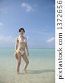站立在蓝色海的泳装妇女 1372656