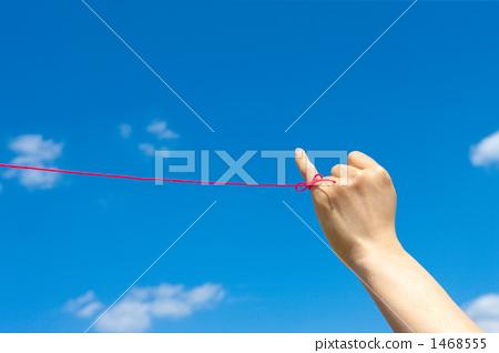 젊은 여성의 왼손 새끼 손가락에서 붉은 실이 푸른 하늘에 1468555