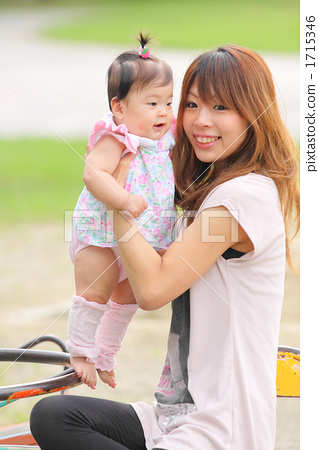 Baby and young mama playing in the park's rotating playground equipment 1715346