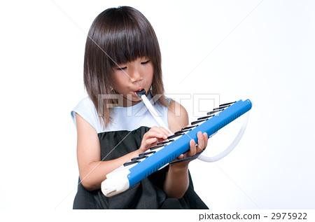 A girl playing a keyboard harmonica 2975922