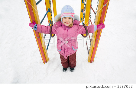 little pretty smiling girl in pink jacket on playground in winte 3587052