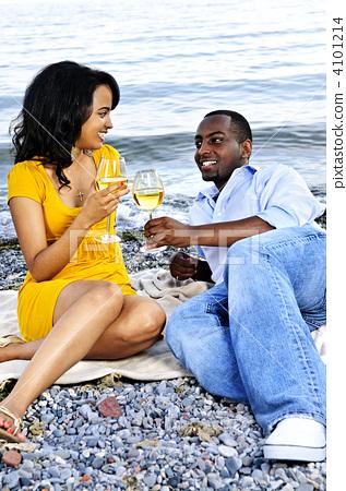 Happy couple having wine on beach 4101214