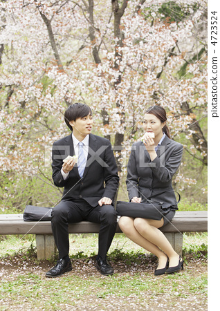 A male and female businessman who is eating a sandwich at a park bench 4723524