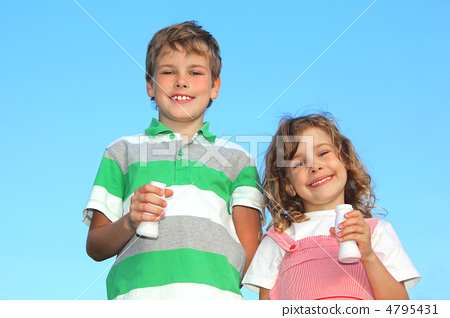 Two children with yoghurt small bottles, smile against the blue 4795431