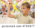 little caucasian boy holding yellow boomerang toy, standing in b 4796877