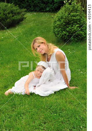 Young mother and daughter resting in meadow 4934415