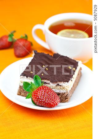 lemon tea, cake and strawberries lying on the orange fabric 5087929