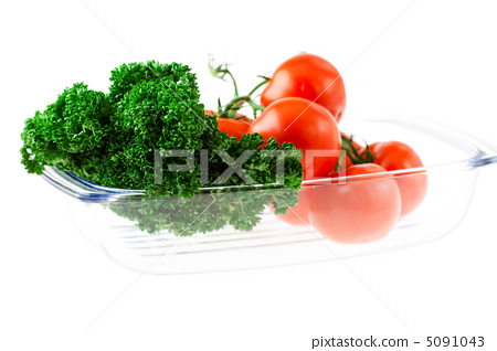 tomatoes and greens with water drops in a glass 5091043