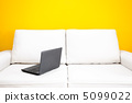 white sofa and laptop against a yellow wall in the apartment 5099022