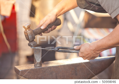 hammer, anvil and the hands of a blacksmith 5099846