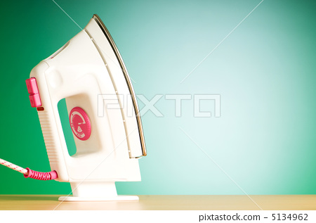 Modern electric iron against the colorful background 5134962