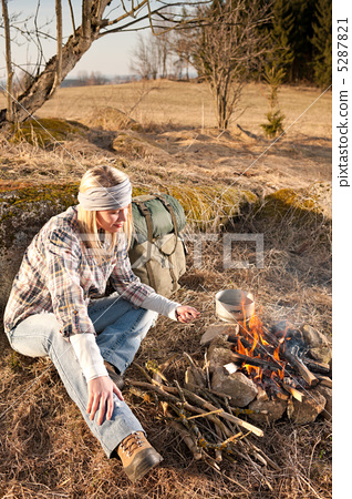 Hiking woman with backpack cook by campfire 5287821