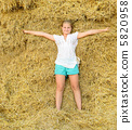 Girl on the background of the large stack of hay 5820958