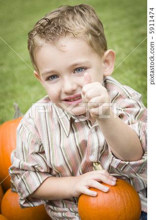 Cure Young Child Boy Enjoying the Pumpkin Patch. 5911474
