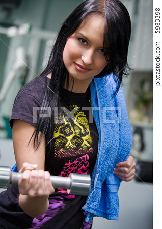 Young smiling woman with a dumbbell 5983398