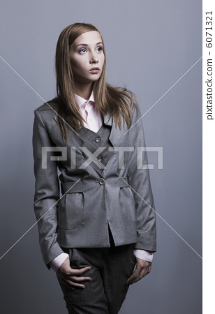 Trendy fashion model posing in grey costume. Studio shot 6071321