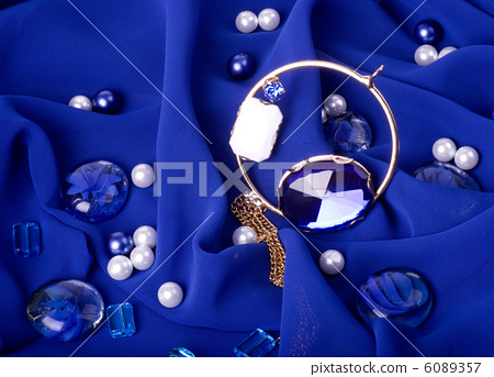 Golden jewelry on blue background 6089357