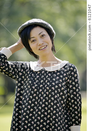A woman holding a hat 6121047