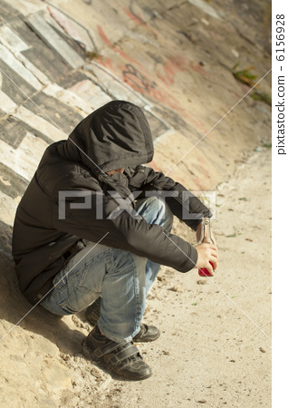 A boy with a hand bottle sits on the concrete wall 6156928