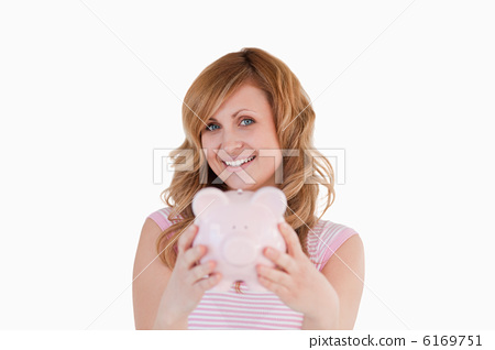 Cute woman posing while holding her piggybank 6169751