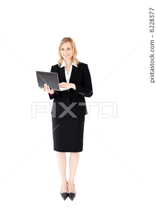 Self-assured woman using her laptop standing 6228377
