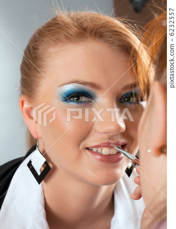 paints professional visagiste with red  lipstick. 6232557