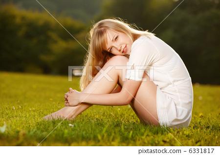 Beautiful blond girl on a grass 6331817
