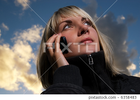 Girl talking to the phone over blue cloudy sky 6358483