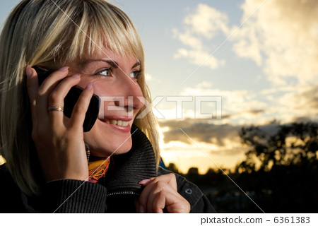 Yong girl talks on the phone outdoors 6361383