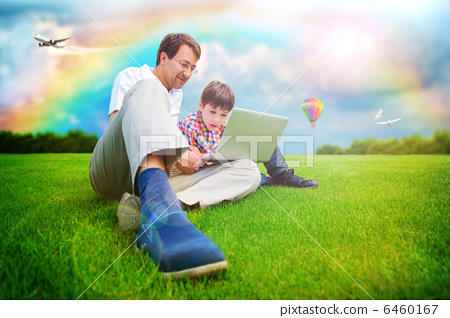 Adult man and his little son sitting on a grass at park and havi 6460167