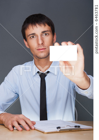 Business man handing a blank business card over grey background 6463781