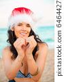 Young beautiful woman wearing christmas hat showing heart shape 6464427