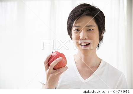A young man with an apple 6477941