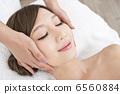 A woman receiving facial beauty treatment 6560884