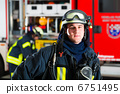 young fireman in uniform in front of firetruck 6751495