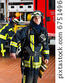 young fireman in uniform in front of firetruck 6751496