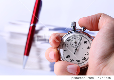 Stopwatch in hand on background of paper cards 6768780