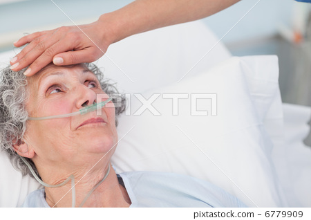 Nurse touching the forehead of a patient 6779909