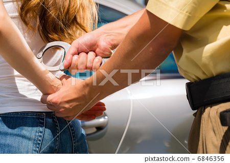 Police officer arresting a woman with handcuffs 6846356