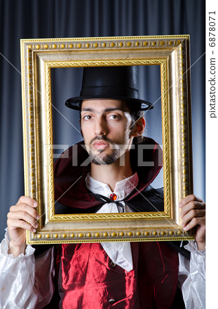Magician with photoframe in studio 6878071