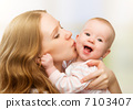 Happy cheerful family. Mother and baby kissing 7103407