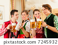 Young people in traditional Bavarian Tracht in restaurant or pub 7245932